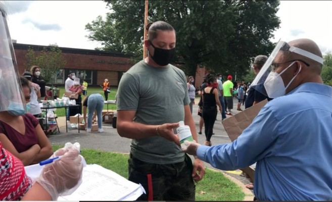 At a distribution of free PPE to indigenous people of the DC metro area, a Masks For America volunteer gives Nurses Station Hand Sanitizer to a community member. Photograph: Sebi Medina-Tayac